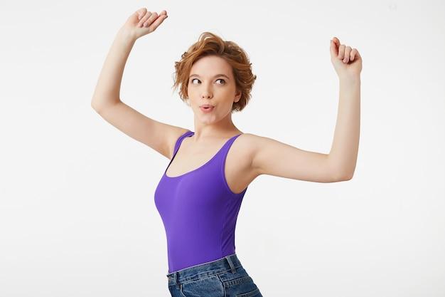 """Młoda atrakcyjna krótkowłosa dziewczyna, ubrana w fioletową koszulkę, tańcząca z podniesionymi rękami i ciesząc się swoim hobby, mówi ustami """"wow"""" na białym tle."""