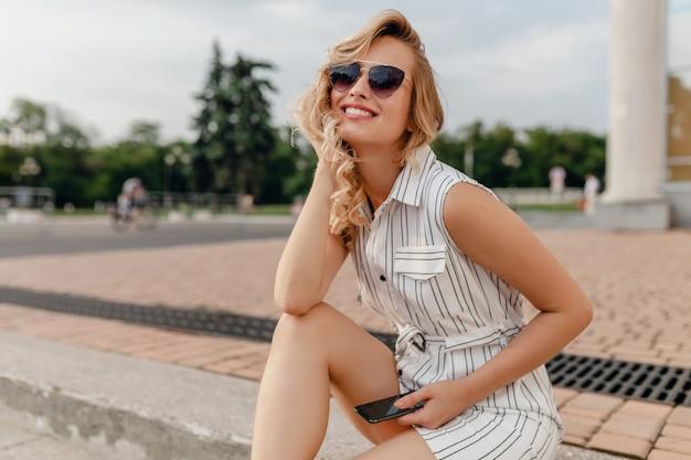 Młoda atrakcyjna ładna stylowa blond kobieta siedzi na ulicy miasta w letniej mody w białej bawełnianej sukience w okularach przeciwsłonecznych