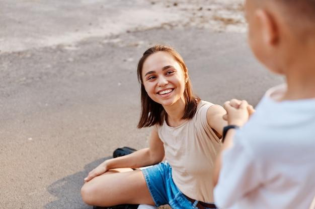 Młoda atrakcyjna matka z synem na rolkach, aktywna koncepcja rodziny. skup się na uśmiechniętej kobiecie, mały chłopiec pomaga mamie wstać z asfaltowej drogi.