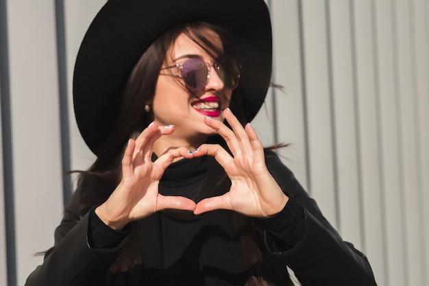 Młoda atrakcyjna modelka w czarnym kapeluszu i okularach przeciwsłonecznych pokazująca dłonie w kształcie serca, pozująca na ulicy