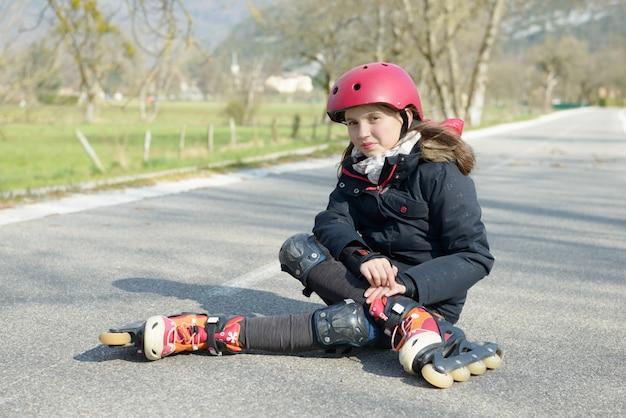 Młoda atrakcyjna nastoletnia łyżwiarz skrzywi się w bólu po upadku
