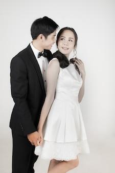 Młoda atrakcyjna para azjatyckich, panna młoda i pan młody, kobieta ubrana w białą suknię ślubną. mężczyzna ubrany w czarny smoking, stojący razem. koncepcja fotografii przedślubnej.