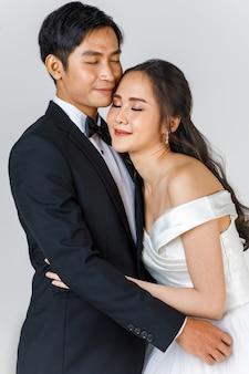 Młoda atrakcyjna para azjatyckich, wkrótce panna młoda i pan młody, kobieta ubrana w białą suknię ślubną. mężczyzna ubrany w czarny smoking, przytulający się do siebie. koncepcja fotografii przedślubnej.