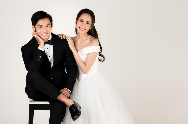Młoda atrakcyjna para azjatyckich, wkrótce panna młoda i pan młody, kobieta ubrana w białą suknię ślubną. mężczyzna ubrany w czarny smoking, siadający razem. koncepcja fotografii przedślubnej.
