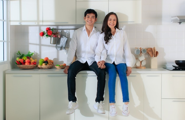 Młoda atrakcyjna para azji na sobie białą koszulę i dżinsy, siedząc w białej kuchni.