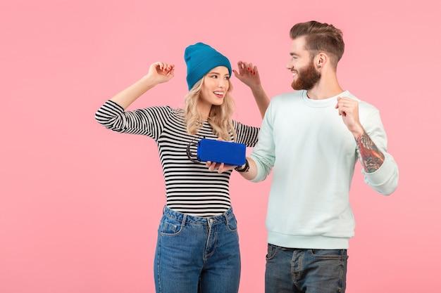 Młoda atrakcyjna para słuchanie muzyki na głośniku bezprzewodowym na sobie fajny stylowy strój uśmiechnięty szczęśliwy pozytywny nastrój pozowanie na różowej ścianie na białym tle taniec zabawy