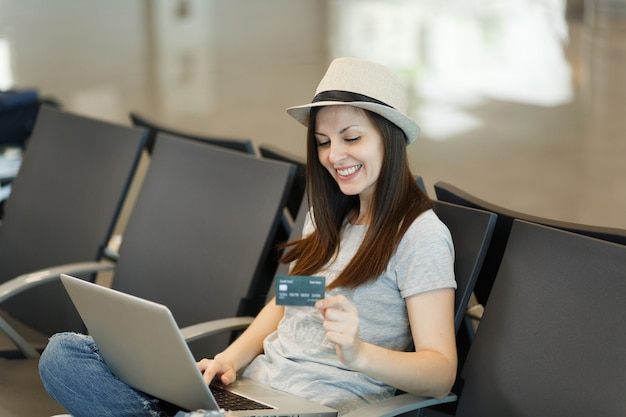 Młoda atrakcyjna podróżniczka turystyczna kobieta w kapeluszu ze skrzyżowanymi nogami, pracująca na laptopie trzymaj kartę kredytową czekaj w holu na lotnisku