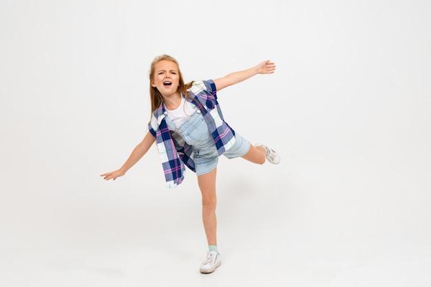 Młoda atrakcyjna powabna caucasian dziewczyna skacze w przypadkowych ubraniach na bławym pracownianym tle