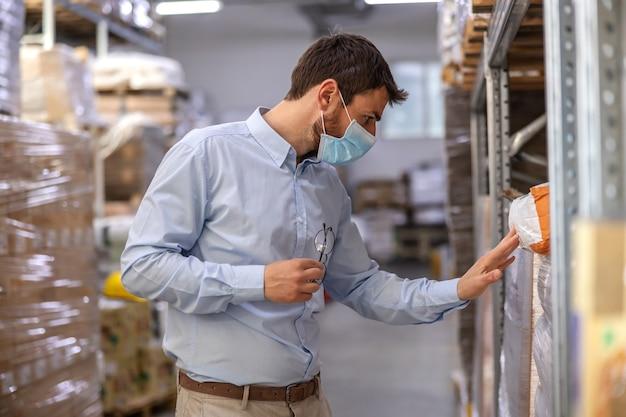 Młoda atrakcyjna przełożona z maską chirurgiczną na stojąco w magazynie i sprawdzaniu towarów. koncepcja wybuchu koronawirusa.