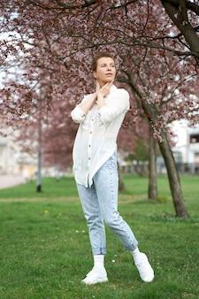 Młoda atrakcyjna ruda kobieta ubrana w białą stylową bluzkę i dżinsy, pozowanie na tle kwitnącej sakury.