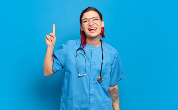 Młoda atrakcyjna rudowłosa kobieta czuje się jak szczęśliwy i podekscytowany geniusz po zrealizowaniu pomysłu, radośnie podnosząc palec, eureka !. koncepcja pielęgniarki szpitalnej