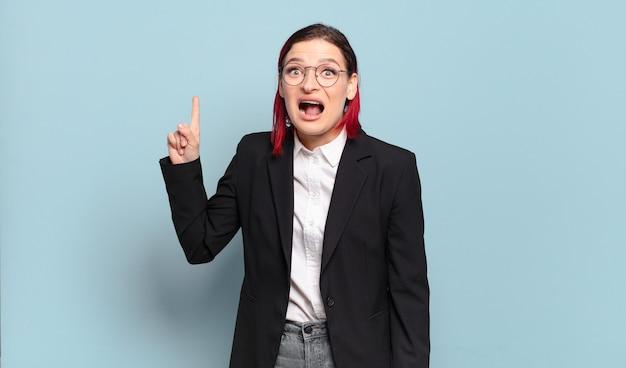 Młoda atrakcyjna rudowłosa kobieta czuje się jak szczęśliwy i podekscytowany geniusz po zrealizowaniu pomysłu, radośnie unosząc palec, eureka!