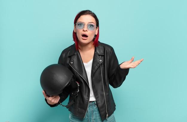 Młoda atrakcyjna, rudowłosa kobieta czuje się niezwykle zszokowana i zaskoczona, niespokojna i spanikowana, ma zestresowany i przerażony wygląd. koncepcja motocyklisty
