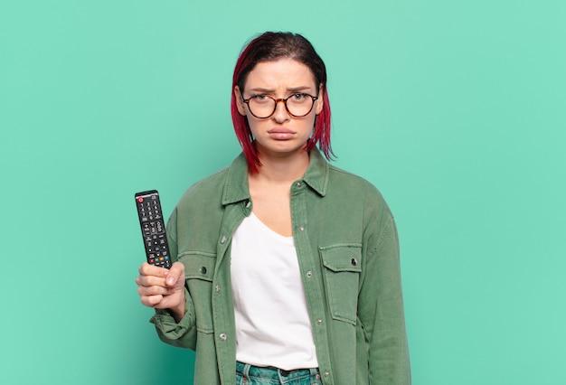 Młoda atrakcyjna rudowłosa kobieta czuje się smutna i jęczy z nieszczęśliwym spojrzeniem, płacze z negatywnym i sfrustrowanym nastawieniem i trzyma pilota do telewizora