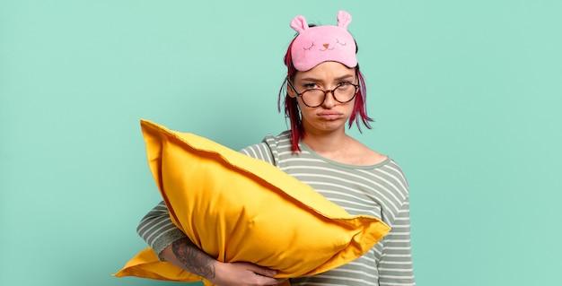 Młoda atrakcyjna rudowłosa kobieta czuje się smutna i marudna z nieszczęśliwym spojrzeniem, płacze z negatywnym i sfrustrowanym nastawieniem i ma na sobie piżamę.