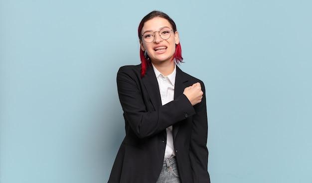 Młoda atrakcyjna rudowłosa kobieta czuje się szczęśliwa, pozytywna i odnosząca sukcesy, zmotywowana, gdy staje przed wyzwaniem lub świętuje dobre wyniki