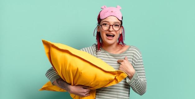 Młoda atrakcyjna rudowłosa kobieta czuje się szczęśliwa, zaskoczona i dumna, wskazując na siebie z podekscytowanym, zdumionym spojrzeniem i ubrana w piżamę.