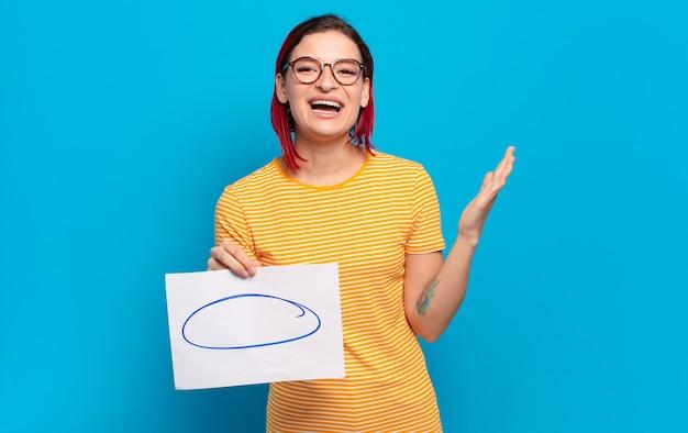 Młoda atrakcyjna rudowłosa kobieta czuje się szczęśliwa, zaskoczona i wesoła, uśmiechając się z pozytywnym nastawieniem, realizując rozwiązanie lub pomysł