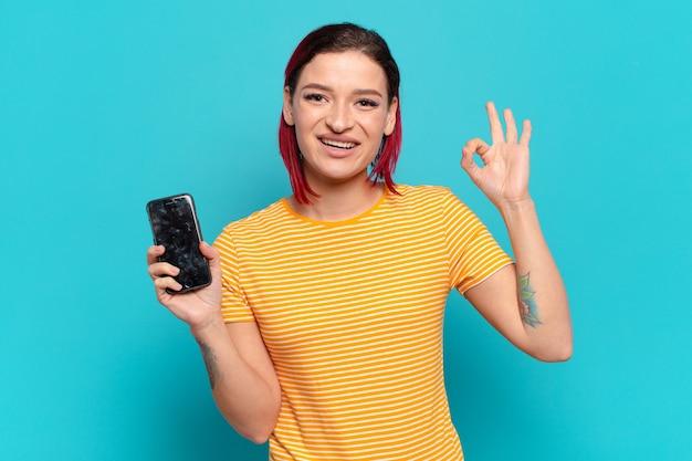 Młoda atrakcyjna rudowłosa kobieta czuje się szczęśliwa, zrelaksowana i zadowolona, okazując aprobatę dobrym gestem, uśmiechając się i pokazując swoją komórkę