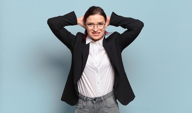 Młoda atrakcyjna rudowłosa kobieta czuje się zestresowana, zmartwiona, niespokojna lub przestraszona, z rękami na głowie, panikując z powodu błędu