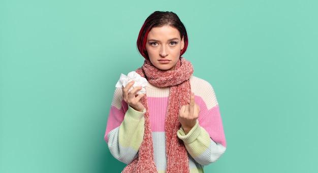 Młoda atrakcyjna rudowłosa kobieta czuje się zła, zirytowana, buntownicza i agresywna, machając środkowym palcem, walcząc z koncepcją grypy