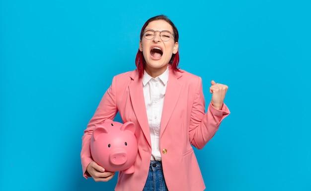 Młoda atrakcyjna rudowłosa kobieta krzyczy agresywnie z gniewnym wyrazem twarzy lub z zaciśniętymi pięściami świętuje sukces. humorystyczny koncepcja biznesowa.