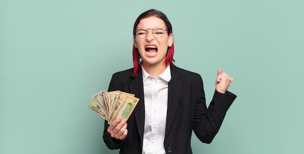 Młoda atrakcyjna rudowłosa kobieta krzyczy agresywnie z gniewnym wyrazem twarzy lub z zaciśniętymi pięściami świętuje sukces. koncepcja pieniędzy