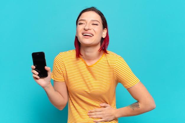 Młoda atrakcyjna rudowłosa kobieta śmiejąca się głośno z jakiegoś zabawnego żartu