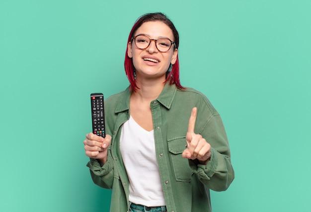 Młoda atrakcyjna rudowłosa kobieta uśmiecha się dumnie i pewnie, triumfalnie wykonując pozę numer jeden, czując się jak lider i trzymając pilota do telewizora