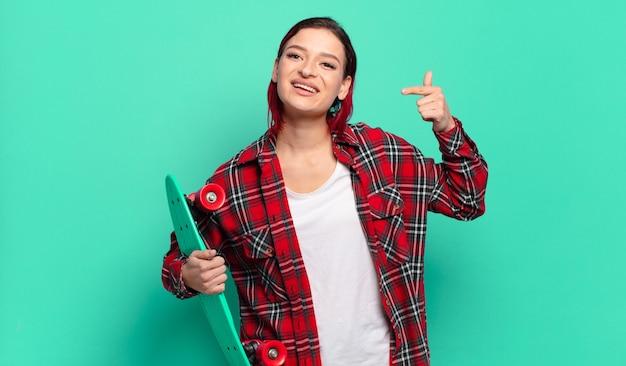Młoda atrakcyjna rudowłosa kobieta uśmiecha się pewnie, wskazując na swój szeroki uśmiech, pozytywną, zrelaksowaną, zadowoloną postawę i trzymającą deskorolkę