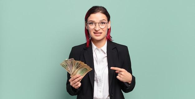 Młoda atrakcyjna rudowłosa kobieta uśmiecha się radośnie, czuje się szczęśliwa i wskazuje na bok i do góry, pokazując obiekt w przestrzeni kopii. koncepcja pieniędzy