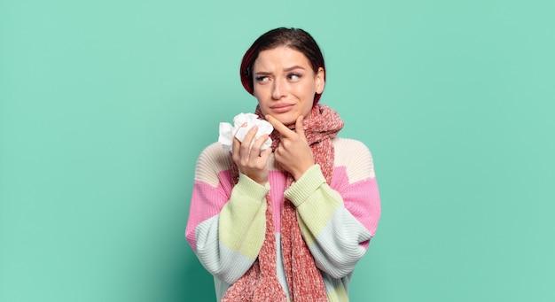 Młoda atrakcyjna rudowłosa kobieta uśmiecha się radośnie i marzy lub wątpi, patrząc w bok koncepcji grypy