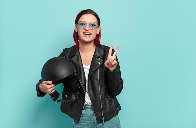 Młoda atrakcyjna rudowłosa kobieta uśmiechająca się i wyglądająca na szczęśliwą, beztroską i pozytywną, gestykulującą zwycięstwo lub pokój jedną ręką