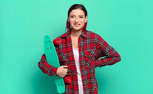 Młoda atrakcyjna rudowłosa kobieta uśmiechająca się szczęśliwie z ręką na biodrze i pewna siebie, pozytywna, dumna i przyjazna postawa oraz trzymająca deskorolkę