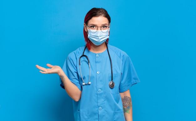 Młoda atrakcyjna rudowłosa kobieta wyglądająca na zaskoczoną i zszokowaną, z opuszczoną szczęką, trzymająca przedmiot z otwartą dłonią na boku. koncepcja pielęgniarki szpitalnej