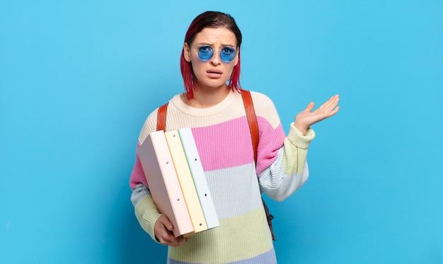 Młoda atrakcyjna rudowłosa kobieta wyglądająca na zaskoczoną i zszokowaną, z opuszczoną szczęką, trzymająca przedmiot z otwartą dłonią na boku. koncepcja studenta uniwersytetu