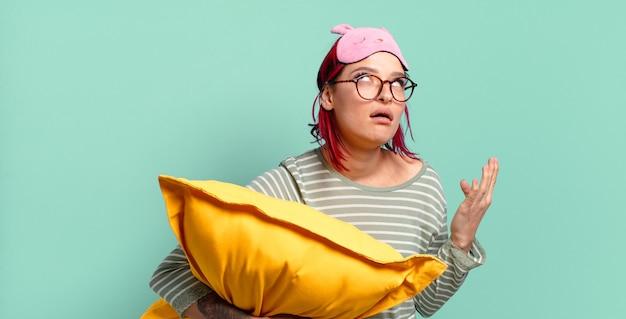 Młoda atrakcyjna rudowłosa kobieta wyglądająca na zdesperowaną i sfrustrowaną, zestresowaną, nieszczęśliwą i zirytowaną, krzyczącą i krzyczącą i noszącą piżamę.