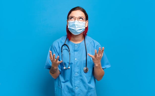 Młoda atrakcyjna rudowłosa kobieta wyglądająca na zdesperowaną i sfrustrowaną, zestresowaną, nieszczęśliwą i zirytowaną, krzyczącą i krzyczącą. koncepcja pielęgniarki szpitalnej