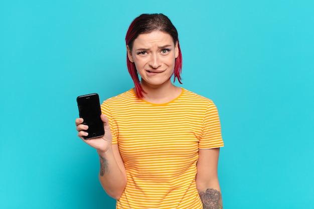 Młoda atrakcyjna rudowłosa kobieta wyglądająca na zdziwioną i zdezorientowaną, przygryzając wargę nerwowym gestem, nie znając odpowiedzi na problem i pokazując swoją komórkę
