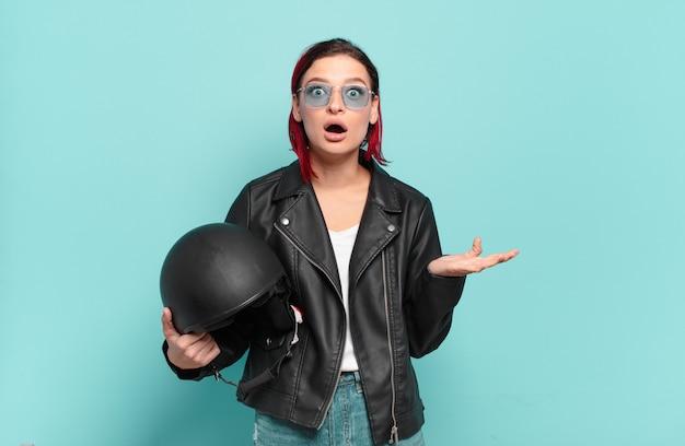 Młoda atrakcyjna rudowłosa kobieta z otwartymi ustami i zdumiona, zszokowana i zdumiona niewiarygodną niespodzianką. koncepcja motocyklisty