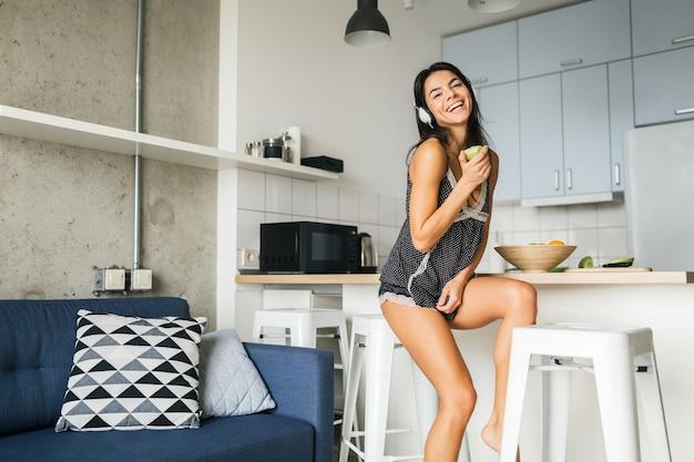 Młoda atrakcyjna seksowna kobieta rano je śniadanie w stylowej nowoczesnej kuchni, jedzenie jabłka, uśmiechnięty, szczęśliwy, pozytywny, zdrowy styl życia, słuchanie muzyki na słuchawkach, śmiech, dobra zabawa