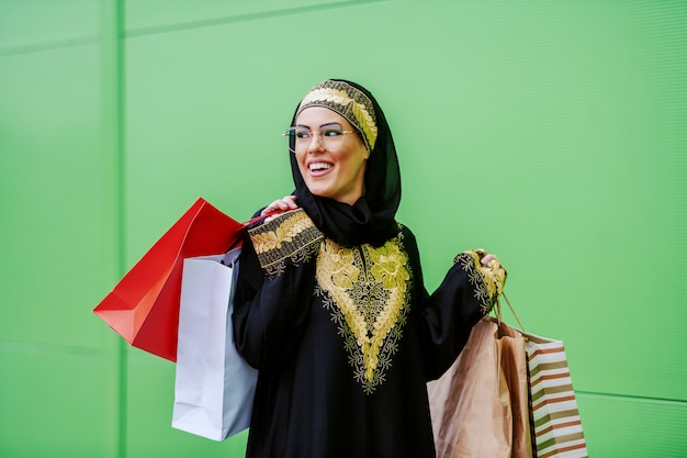 Młoda atrakcyjna śmiejąca się arabka w tradycyjnej odzieży spaceru na świeżym powietrzu z torby na zakupy w ręce. jest zadowolona z zakupów.