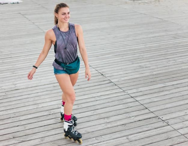 Młoda atrakcyjna sport kobieta na rolkach na plaży