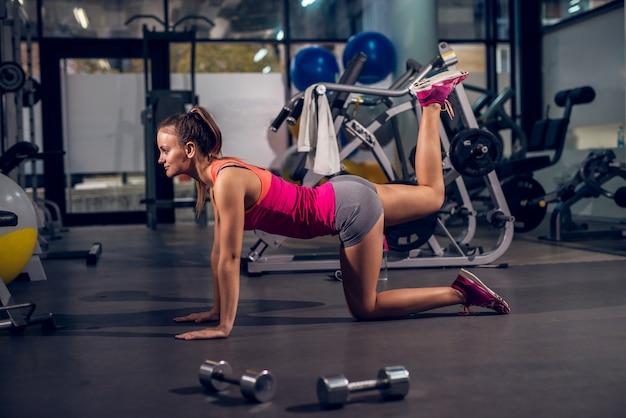 Młoda atrakcyjna sportowa dziewczyna aktywna klęcząca na podłodze, podnosząc jedną nogę do góry na siłowni.