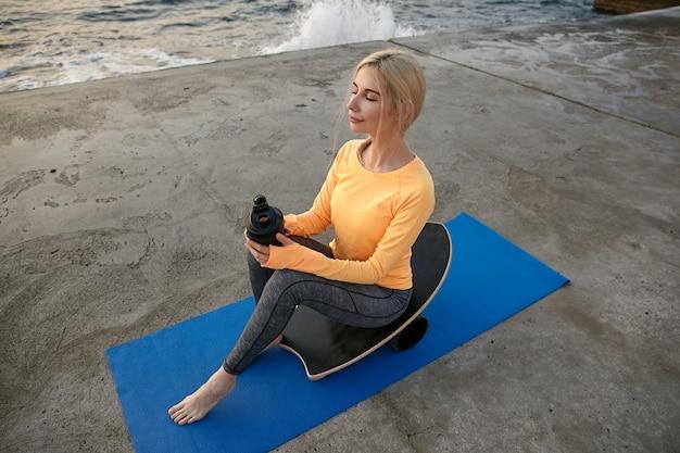 Młoda atrakcyjna sportowa kobieta o blond włosach uprawiająca sport nad morzem, siedząca na równoważni i trzymająca shaker z białkiem, patrząc na bok w zamyśleniu