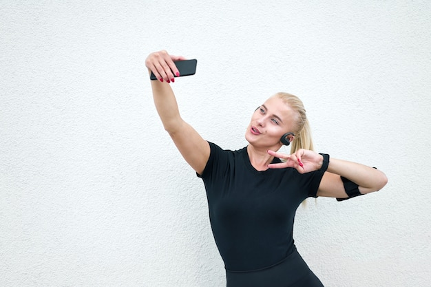 Młoda atrakcyjna sporty dziewczyna jest ubranym czarnego sportswear słucha muzyka i rozciąga na biel ściany tle. koncepcja aktywnego i zdrowego życia.