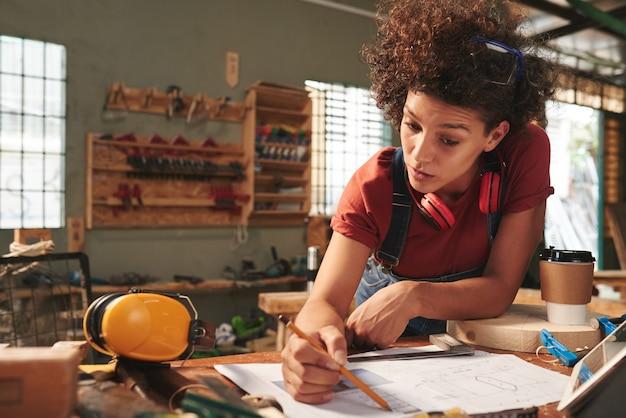 Młoda atrakcyjna stolarz dokładnie sprawdza pomiary na planie przed rozpoczęciem pracy z drewnem