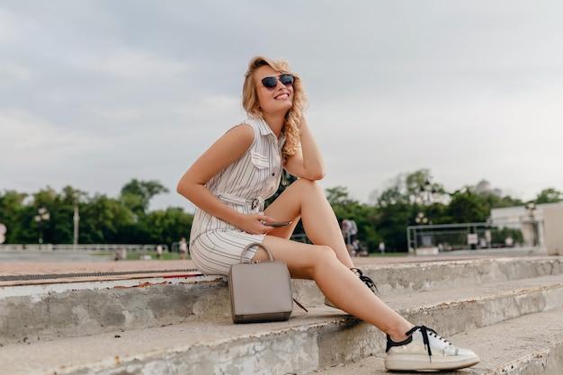 Młoda atrakcyjna stylowa blondynka siedzi na ulicy miasta w letniej sukience w stylu mody na sobie okulary przeciwsłoneczne, torebkę, srebrne trampki