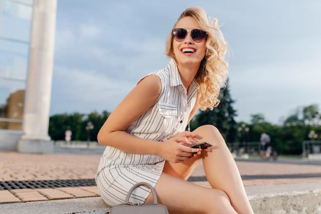 Młoda atrakcyjna stylowa blondynka siedzi na ulicy miasta w letniej sukience w stylu mody na sobie okulary przeciwsłoneczne, trzymając telefon, śmiejąc się szczerze
