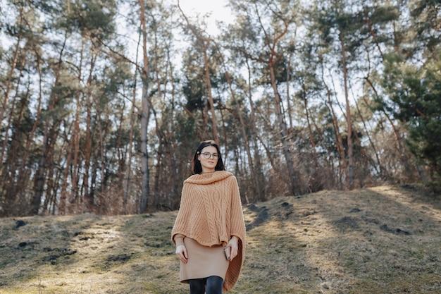Młoda atrakcyjna stylowa dziewczyna na charakter na tle lasu z telefonu w słoneczny dzień